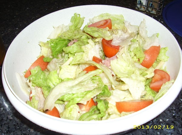 Toss all salad ingredients in a bowl, except Romano Cheese.