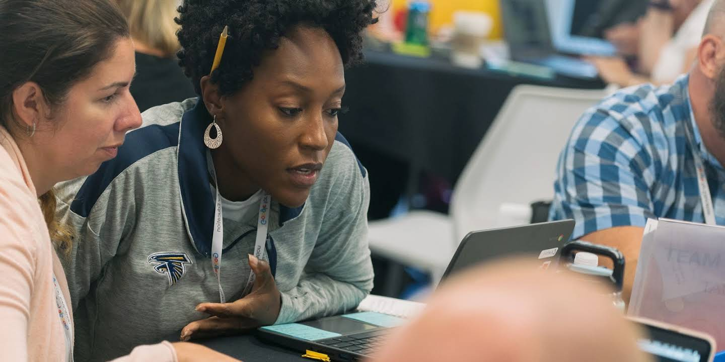Two educators discuss something in front of a Chromebook.