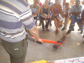 Photo: Dr. Miquel Socorro describing the mechanical weeder to a group of farmers. (Photo by Rena Perez)