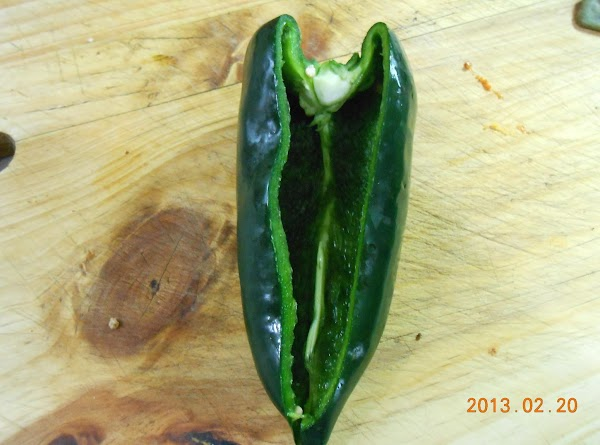 Make a V shaped slit in poblano pepper, remove, and remove seeds and stem.