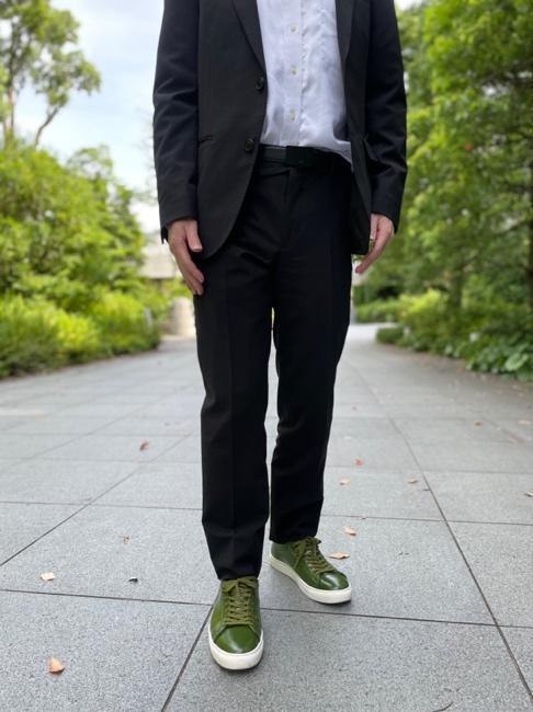 歩道に立っているスーツを着た男性  中程度の精度で自動的に生成された説明