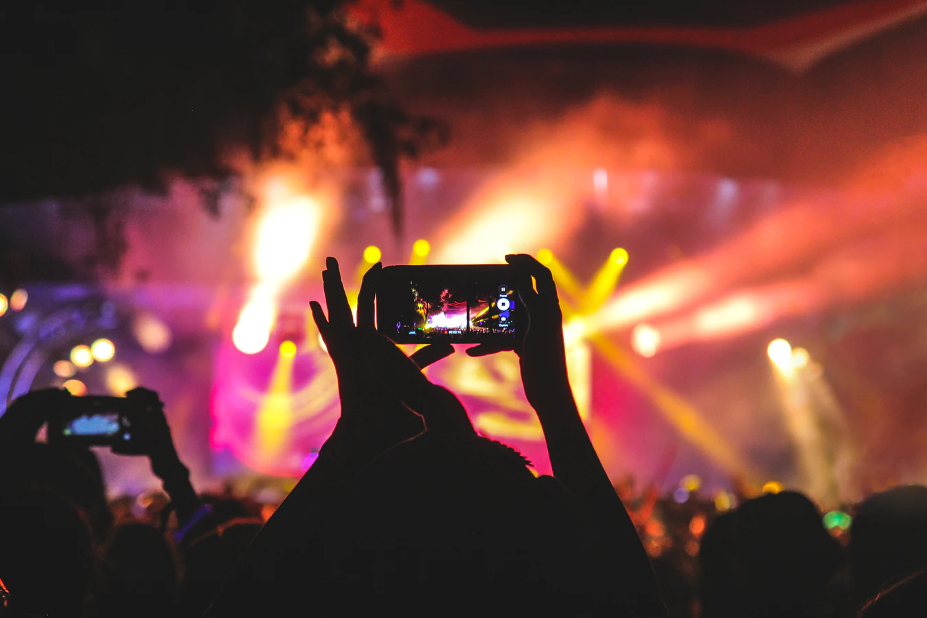 Concert goer taking video of stage on smartphone