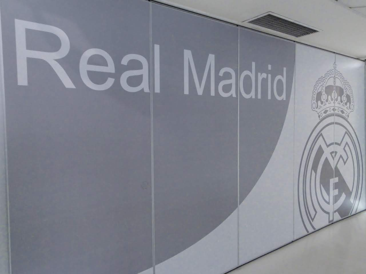 A large padded wall featuring the Real Madrid logo