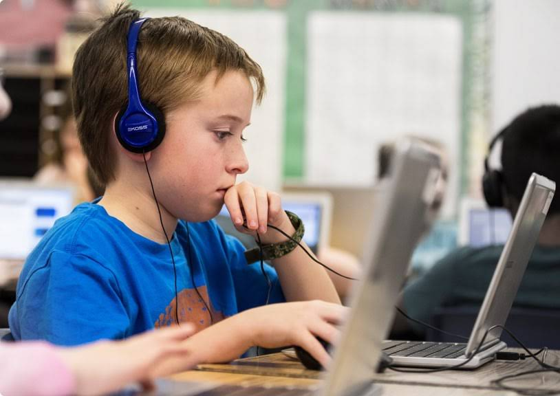 Kid using a Chromebook with headphones.