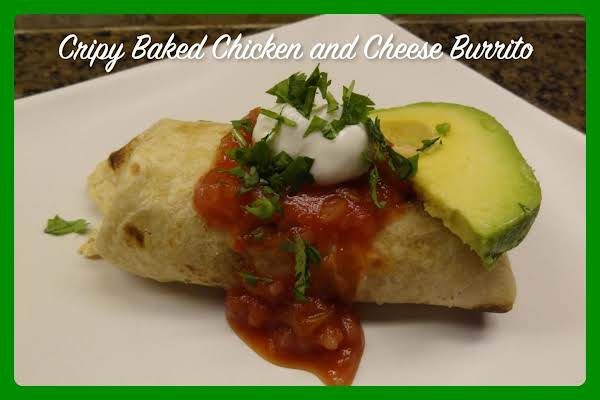 Crispy Baked Chicken And Cheese Burrito Topped With Salsa, Sour Cream, Avocado, And Cilantro