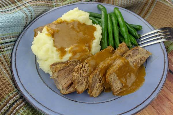 Gingersnap Pot Roast Sliced On A Plate With Gravy.