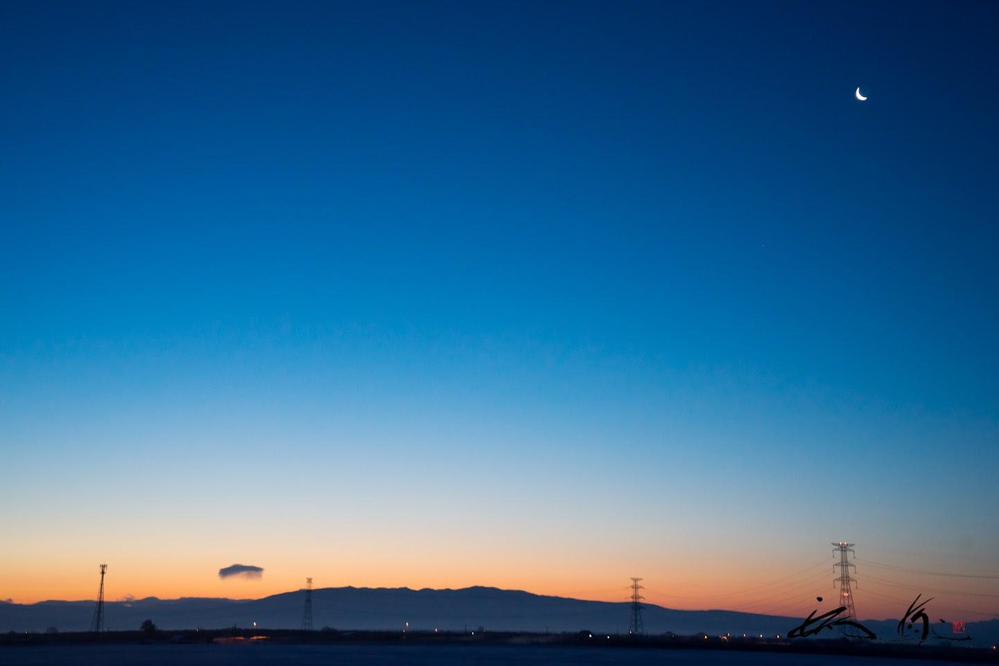 マジックアワーの瑠璃色の空に浮かぶ三日月