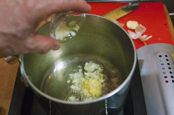 When the oil begins to shimmer, add the garlic, ginger, and green onions, and...