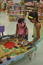 Photo: After all that hard work shopping, my girls and Daddy take a little break at the train table.  I love when stores have toys that the kids can actually play with in the store.