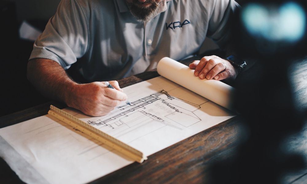 Man laying out furniture on a blue print of a room