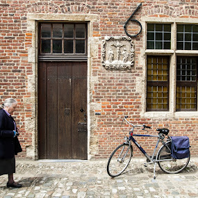 Old lady  passes wooden door and parked bicycle in Grand Beguinage of Leuven, Belgium.  Grand Beguinage of Leuven is included in the list of world heritage of UNESCO and also a popular tourist attraction. by Max Mayorov - People High School Seniors ( flanders, leuven, old, walking, europe, beguinage, brick, street, door, architecture, house, bicycle, béguinage, bike, cobblestones, transport, woman, tradition, classic, building, louvain, groot begijnhof, belgium, traditional, grand béguinage, history, landmark, urban, window, outdoors, monastery, lady, town, historical, begijnhof, big, walk, medieval, wall )