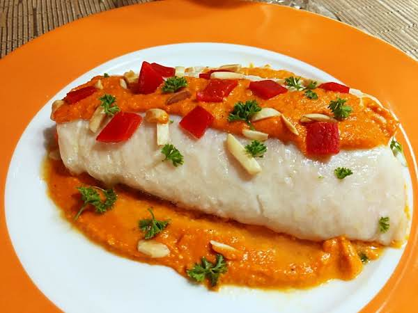 A Fish Fillet Topped With A Red Sauce And Garnished With Slivered Almonds And Roasted Red Peppers.