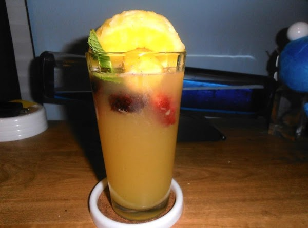 In a tall highball glass, add vodka, juice, champagne, frozen fruit.  Top glass...