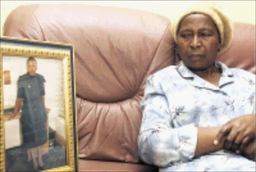 SADDENED: Jubriel Mamotsiri Tladi's mother Anna next to her daughter's framed picture, taken when she was in her police uniform. Pic. Lucky Nxumalo. 22/07/08. © Sowetan.
