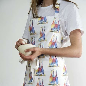 a lady with kitchen apron on it with ducks printed on it