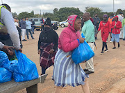 Residents of Mooiplaas informal settlement outside Centurion collect food hampers on Wednesday.