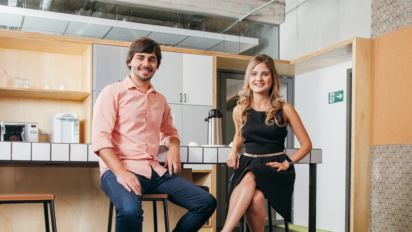 Homem e mulher sentados em bancos em uma cozinha.