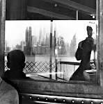 schaduw in raam van mensen in ferry; uitzicht over water op wolkenkrabbers