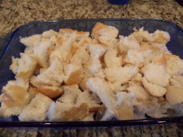 Tear by hand or chop the French bread into 2 inch cubes. Evenly layer...