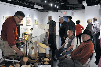 Photo: Clif (left) and Jeff also set up a table full of turning samples to give the members of the public an idea of the diversity of the kinds of things we do.  Eliot Feldman (right), who looks on, is a member of both MCW and WAW (where he has a studio), a fact that led to our initial contact, which has been beneficial to both organizations.  We thank WAW for setting us up in one of their lovely gallery spaces -- the same one that we exhibited in last August.