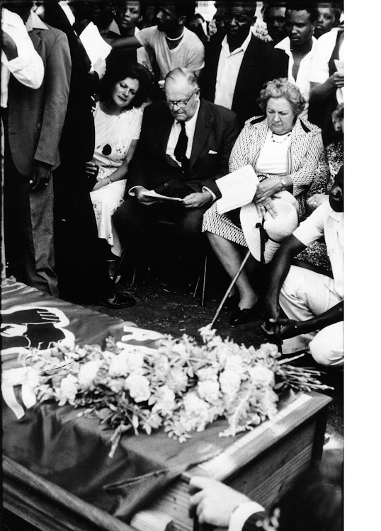 Neil Aggett's parents Aubrey and Joy (since deceased) and sister Jill are joined by mourners at his 1982 funeral. Archive image