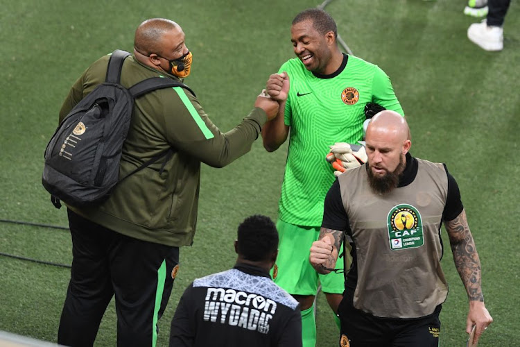 Kaizer Chiefs goalkeeper Itumeleng Khune jokes with club official Jabulani Mbanjani during the match against Wydad Casablanca at FNB Stadium. The club's goalkeeper coach Lee Baxter is also in the picture.
