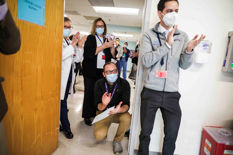 President and CEO of the Boston Medical Center Kate Walsh (C) applauds alongside other employees after the first Covid-19 vaccine is administered to staff at Boston Medical Center in Boston, Massachusetts. Picture: Erin Clark/Pool via REUTERS