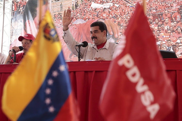 Venezuela's President Nicolas Maduro greets workers behind a PDVSA flag in Morichal, Venezuela. Picture: REUTERS