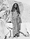 Afrikaanse vrouw met zwarte hoofddoek en lange rok voor een rieten gebouwtje