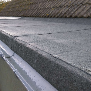 a black flat roof next to roof tiles