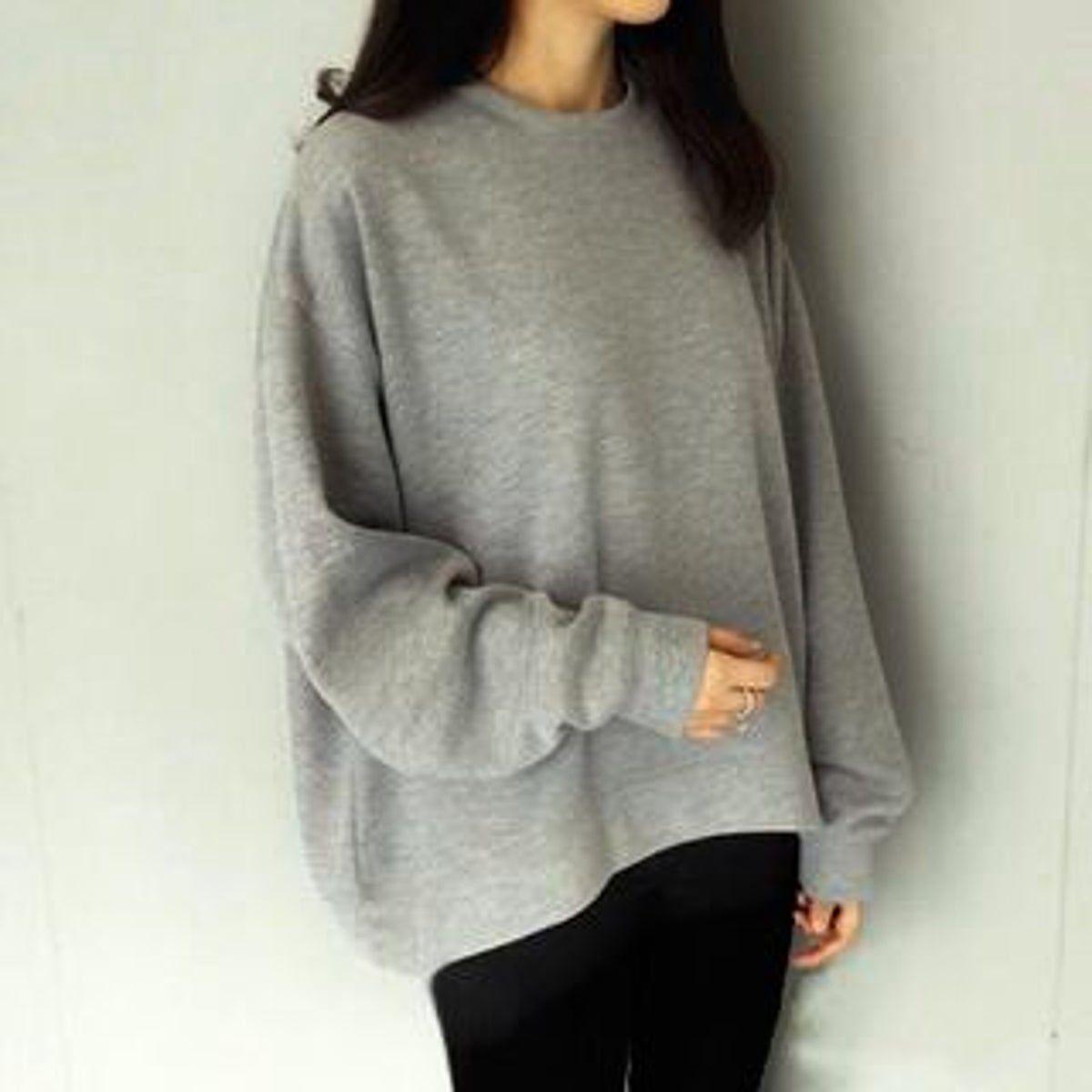 Girl wearing an oversized grey sweatshirt with black leggings.
