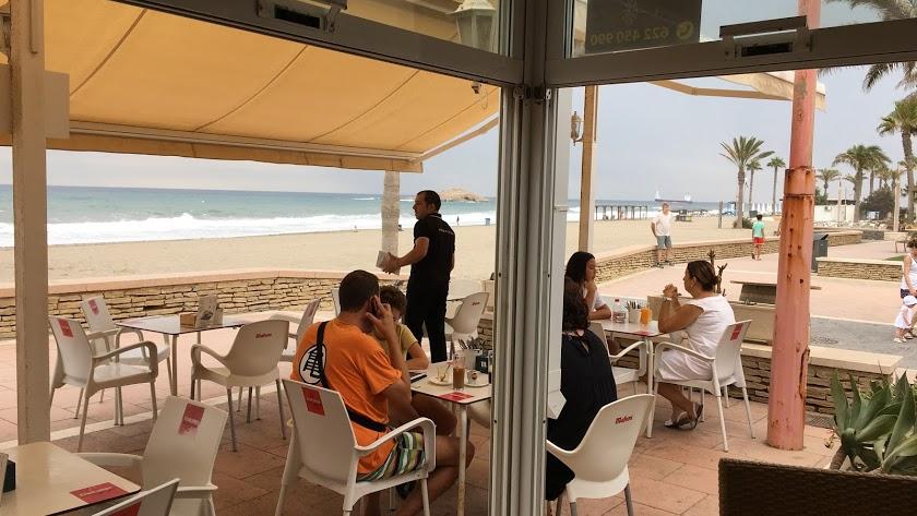 Un camarero atiende una terraza de un bar en el paseo marítimo.