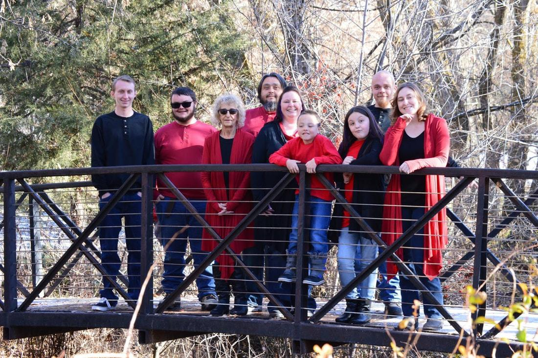 A group of people posing for a photo on a bridge  Description automatically generated with medium confidence