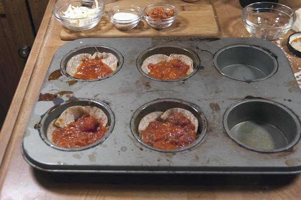 Push into the muffin tin, and add the pizza sauce, and spread over the...