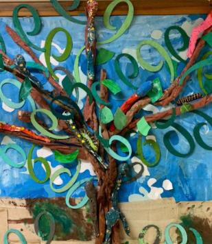 A imagem representa uma árvore, o habitat da lagarta. Ela tem um tronco marrom, folhas verdes e um fundo azul