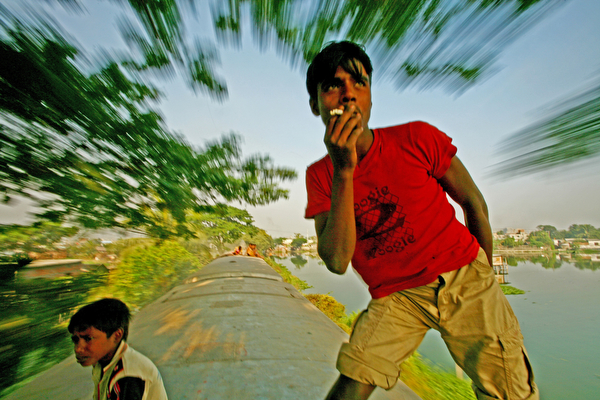 "Photo: It's no problem, watch me smoke and pose for you on a moving train,"" said Helaluddin (18) who frequently travels like this on his off day from the plastic factory where he works. Dhaka, Bangladesh."