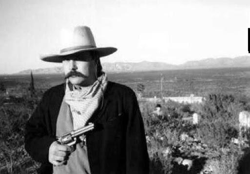 Foto de un vaquero con sombrero y pistola donde aparece un fantasma detras de el