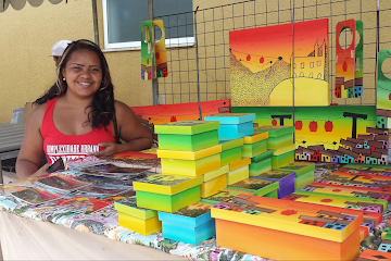 A photo of Mariluce. She sits at a table showcasing the colorful art of her students from the favelas.