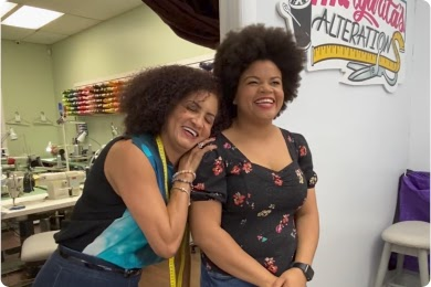 Two women with curly hair embrace at an alterations business, smiling and laughing.
