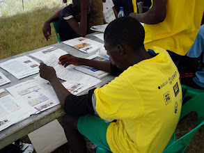 Photo: Young man reading about safe-male circumcision at the SAREP table