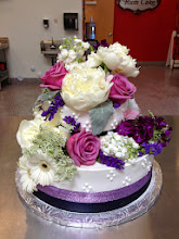 Photo: Floral Wedding Cake: 2-tiers frosted in white, Italian whipped cream. Decor: smooth sides with 4-dot  cluster in white and double ribbon wrap around bottom with plum, satin ribbon (below) and lavender, glitter ribbon (above). Design complete with a floral bouquet of Gerbera, Roses, Peony, Stalk etc. (provided by bride).