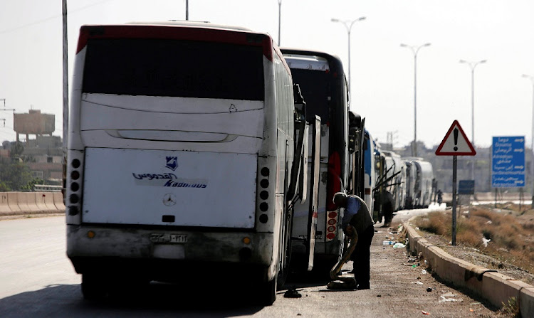 A driver stands next to a bus as he waits to cross into the town of Douma, eastern Ghouta. Picture: REUTERS