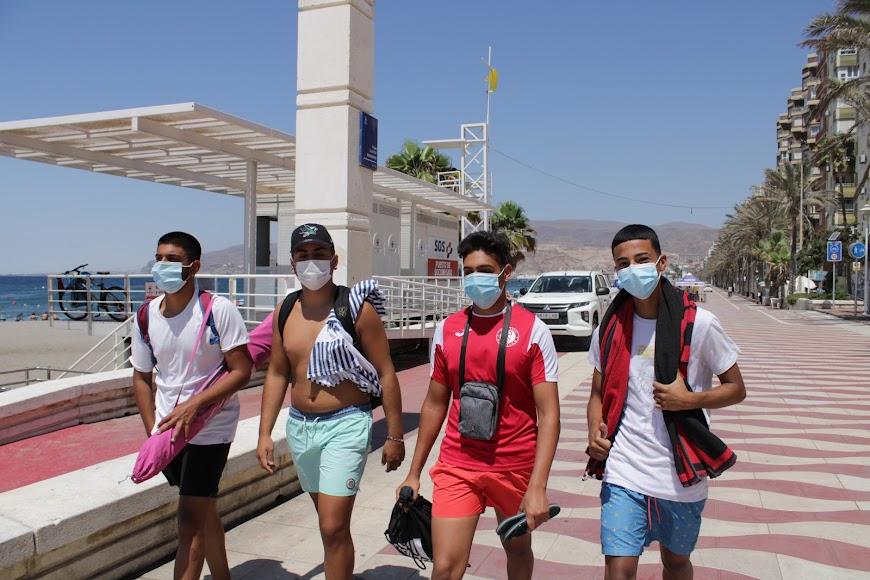 Jóvenes almerienses paseando y con mascarilla por el Paseo Marítimo.
