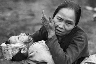 Photo: 11 Feb 1968, Hue, Vietnam --- Original caption: With a wounded baby in her arms, an elderly Vietnamese woman makes a plea for help as she arrives at a U.S. Marine aid station. --- Image by © Bettmann/CORBIS