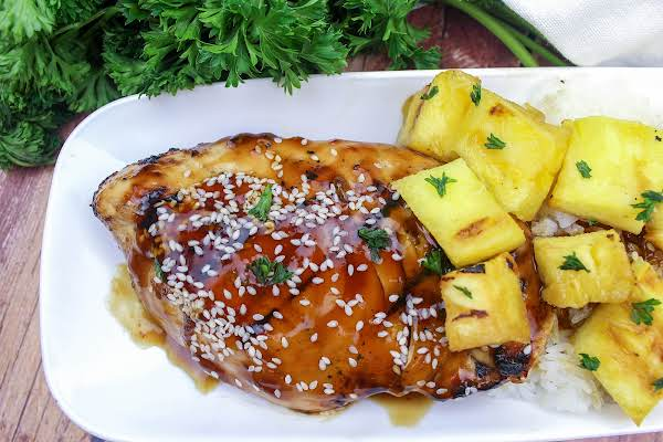 A Piece Of Teriyaki Ginger Chicken On A Plate With Grilled Pineapple.