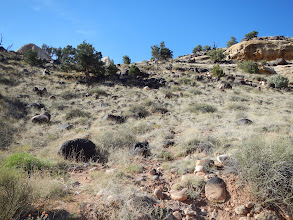 Photo: Black boulders look wildly out of place in this sediment-layer landscape.