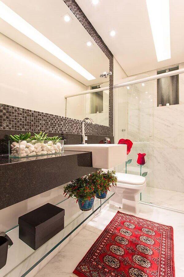 Banheiro com box de vidro, bancada da pia de mármore preto louças branca, prateleira de vidro e pastilhas em faixa decorando ao redor do espelho.