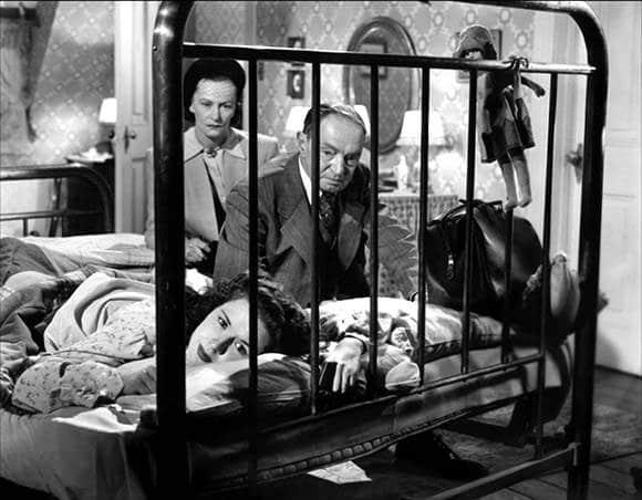 Anne lies face down in her bed, looking distressed. An older man and woman sit beside her, with grave expressions.