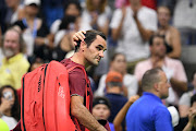 Roger Federer of Switzerland walks off the court after his loss to John Millman of Australia celebrates in a round of 16 match on day eight of the 2018 US Open tennis tournament at USTA Billie Jean King National Tennis Center on September 3, 2018 in New York