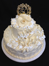 Photo: 2-tier champagne colored frosting base w/matching whipped cream roses & white foliage. Gold 50th anniversary topper.